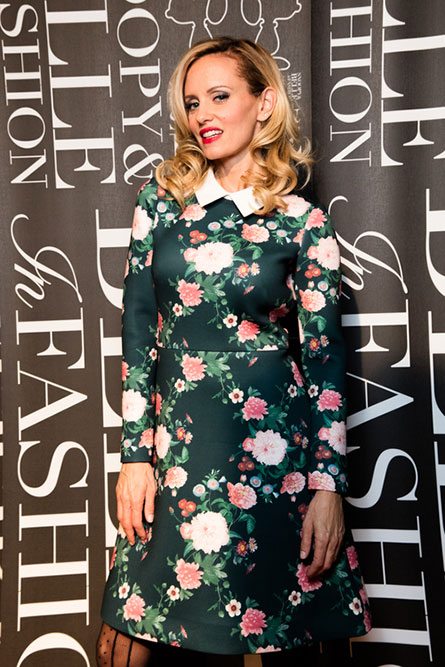 A blonde woman, wearing a colourful dress, standing in front of a black and white poster.