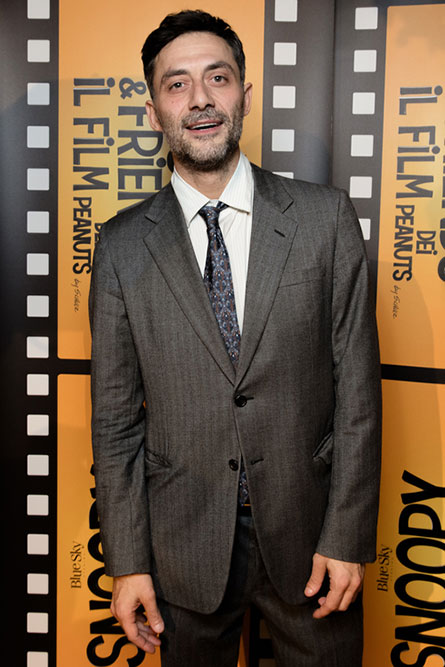 A man wearing a grey suit is standing in front of an orange movie poster and posing for a picture.