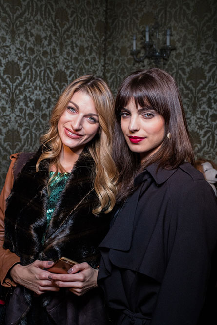 A blonde woman and a brunette woman posing for a photo at an event.