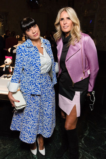A brunette woman, wearing a blue and white dress is standing beside a blonde woman wearing a black dress with a pink jacket. They are posing for a picture at an event.