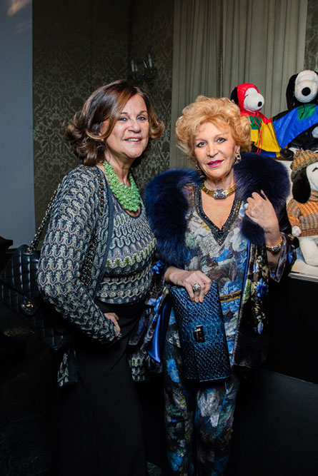 Two senior women standing in front of a display of black and white dog statues and posing for a picture.