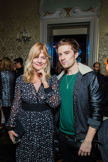 A blonde woman, in a black and white dress, standing next to a man wearing a green shirt and a leather jacket and posing for a photo.