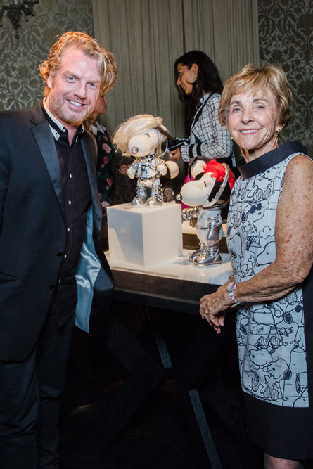 A man and senior woman, dressed in semi-formal attire, standing in front of dog statues and posing for a photo at an event.