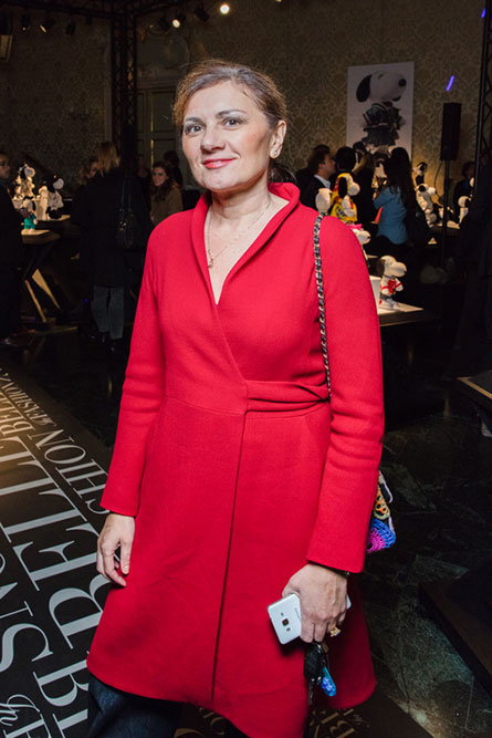 A middle-aged woman, wearing a long sleeve red dress, is posing for a photo at a semi-formal event.