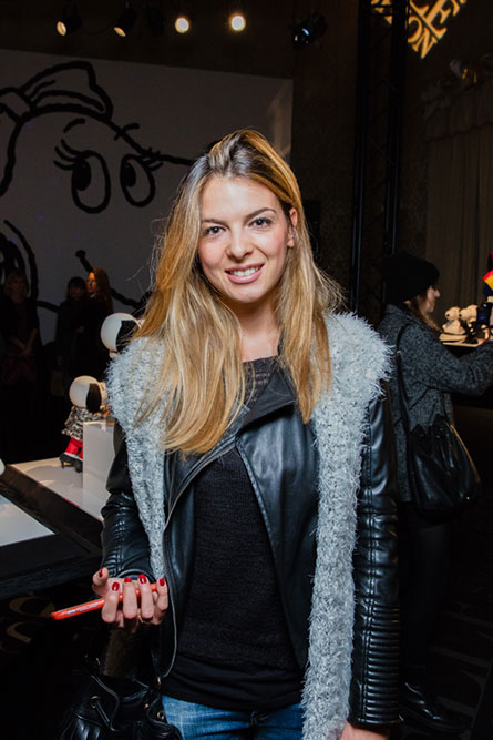 A woman with light brown hair, wearing a black leather jacket, is posing for a photo at an event.