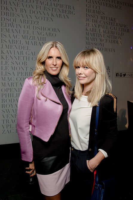 Two middle-aged, blonde women posing for a photo at an event. The woman on the left is wearing a pink jacket and the woman on the right is wearing a white blouse and a black jacket.