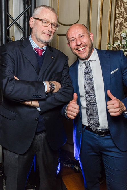 Two men wearing suits posing for a phot at an event. The man on the right is giving two thumbs up and the man on the left has his arms crossed.