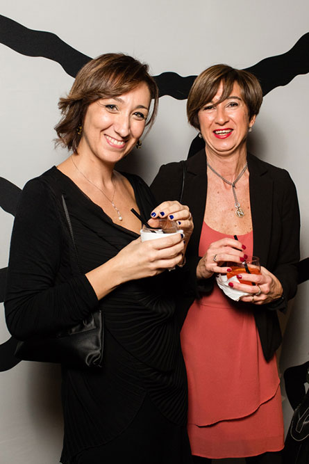 Two middle aged women, wearing semi-formal attire, are holding cocktails in their hands and posing for a photo at an event.
