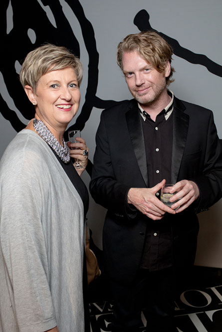 A middle-aged woman with short blonde hair is standing next to a blonde man wearing a black suit. They are posing for a photo at an event.