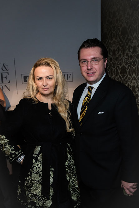 A blonde woman wearing a black dress standing beside a man wearing a black suit and posing for a picture.