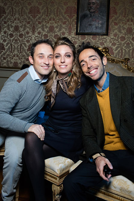 A woman and two men sitting on a couch posing for a photo at a semi formal event.