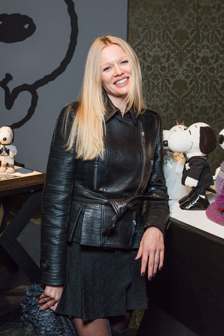 A woman with long blonde hair, wearing a black skirt and leather jacket, is smiling for the camera at a semi formal event.