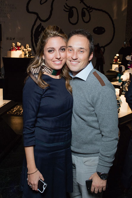 A woman wearing a navy blue dress is standing next to a man wearing a grey sweater. They are posing for a photo at a semi formal event.
