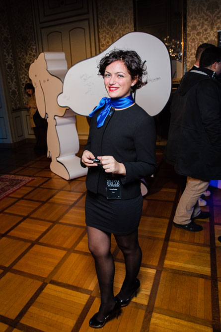 A woman with short black hair, wearing a black dress and a blue scarf, posing for a photo.