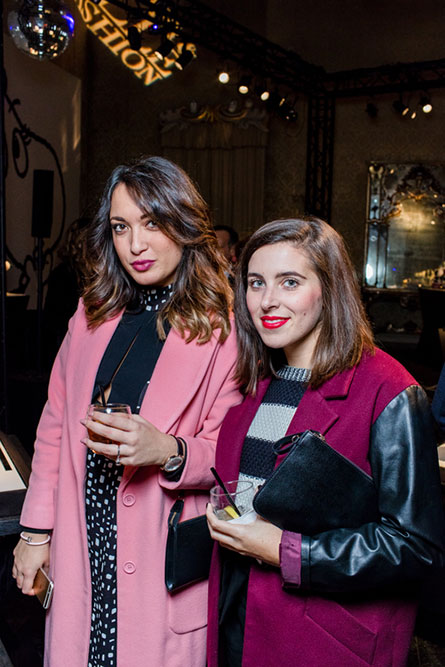 Two women posing for a photo at an event and holding cocktails in their hands. The woman on the left is wearing a light pink coat and the woman on the right is wearing a dark pink coat.