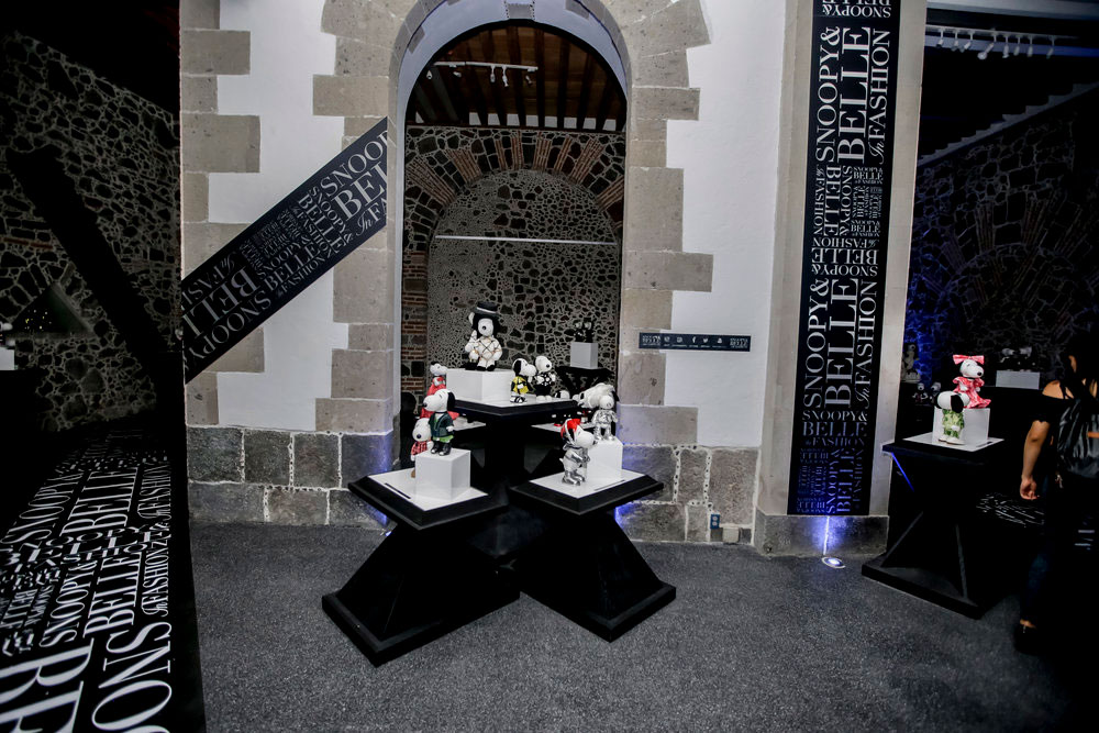 An indoor space with grey carpets, black and white branding and a display of black and white dog statues wearing various costumes.