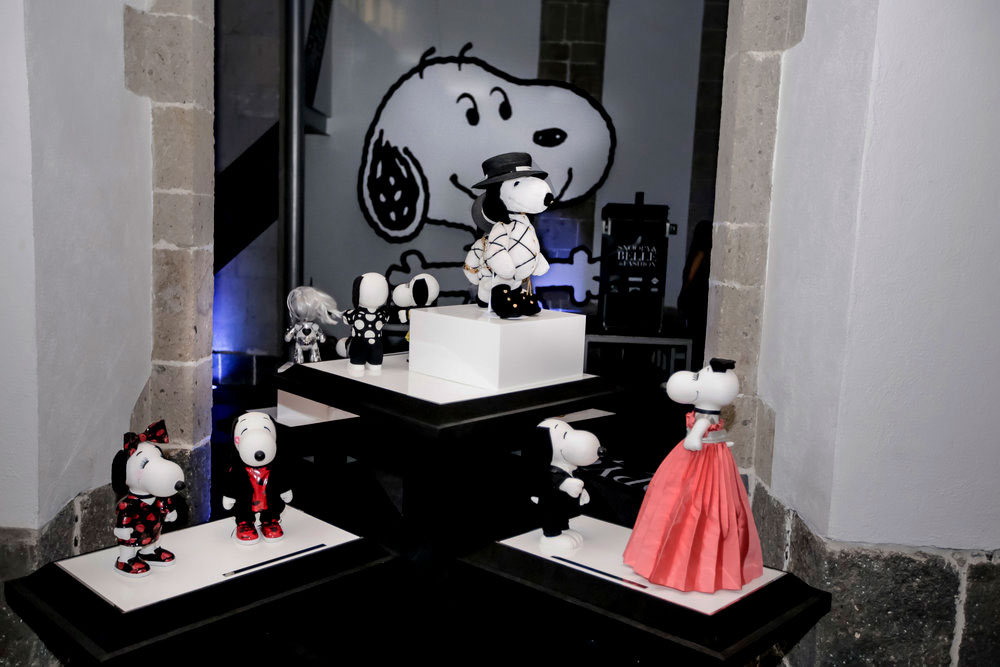Black and white dog statues, wearing various costumes,  displayed on a black and white table.
