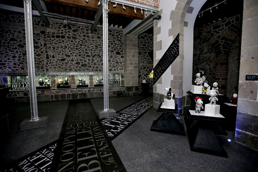 An indoor space with brick walls, grey carpets and glass displays showcasing black and white dog statues wearing various costumes.