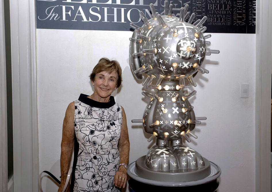 An older woman, wearing a black and white dress, standing beside a large statue of a dog.