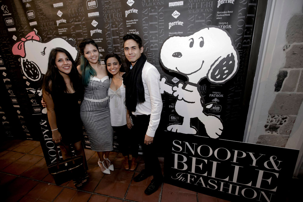 Four people posing in front of a black and white branded wall with a large illustration of a black and white dog.