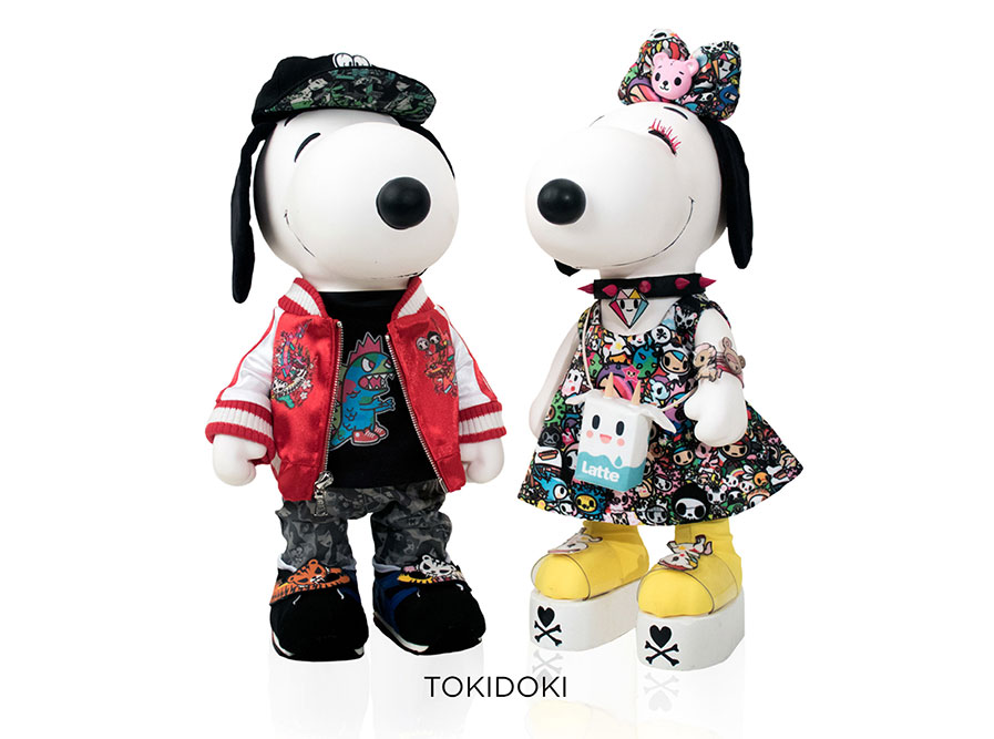 Two black and white, stuffed toy dogs in front of a white background. One is wearing a colourful dress and the other one a red jacket with colourful pants and a baseball hat.