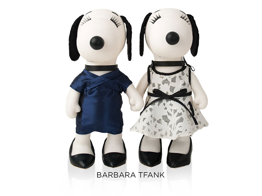 Two black and white, stuffed toy dogs standing and holding hands in front of a white background. The dog on the left is wearing a dark blue dress and the dog on the right is wearing a white dress with black detailing.
