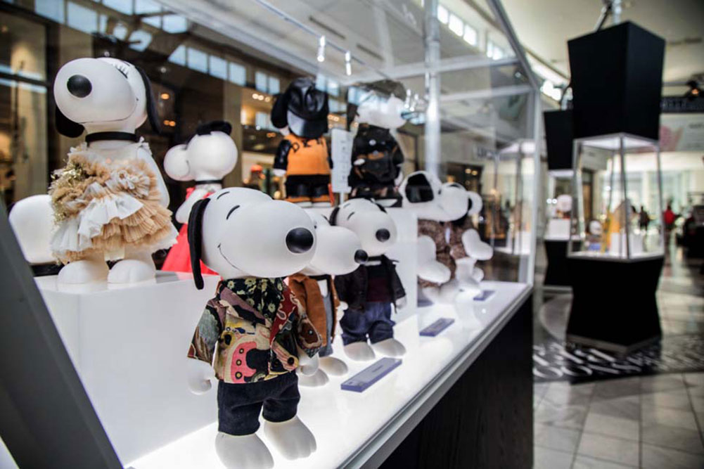 A close-up view inside a glass display showcasing black and white dog statues wearing various outfits.