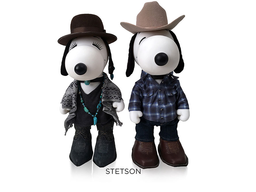 Two black and white, stuffed toy dogs standing in front of a white background wearing cowboy and cowgirl costumes.
