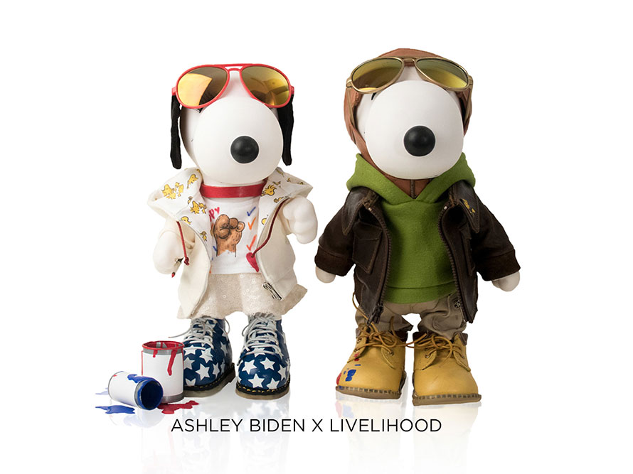 Two black and white, stuffed toy dogs standing in front of a white background. The dog on the left is wearing a beige outfit with red and gold aviators and the dog on the right is wearing a green hoodie, brown leather jacket and red and gold aviators.