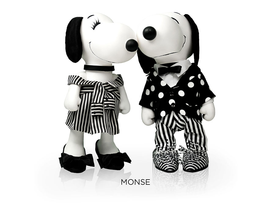 Two black and white, stuffed toy dogs in front of a white background. One is wearing a black and white striped dress and black high heels and the other one a black and white polka dot suit and a bow tie.