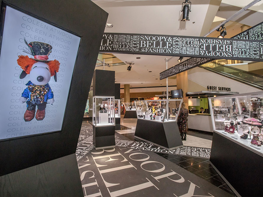 Inside a shopping mall with large glass displays showcasing black and white dog statues. On the left side there is a large screen display of a dog wearing an orange wig and a blue tuxedo.