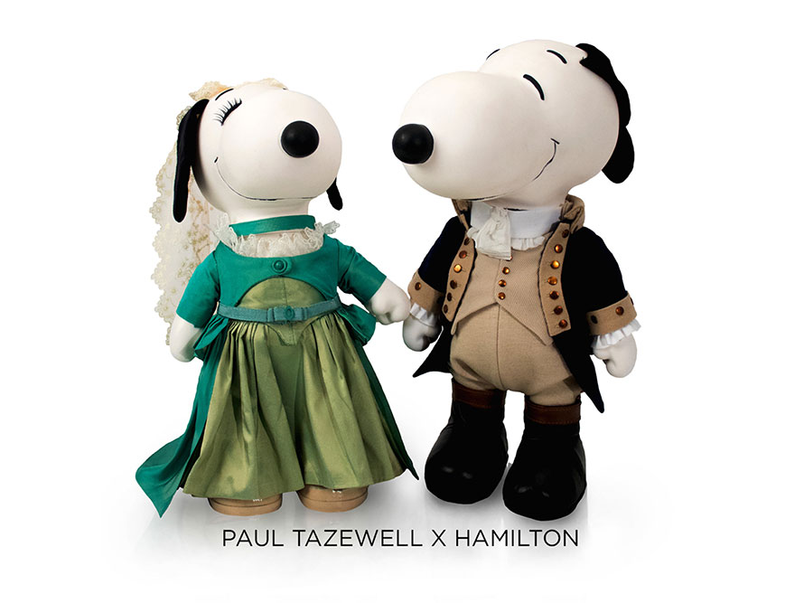 Two black and white dog statues in front of a white background. The dog on the left is wearing a green gown and a veil. The dog on the right is wearing a black tuxedo and a beige vest.