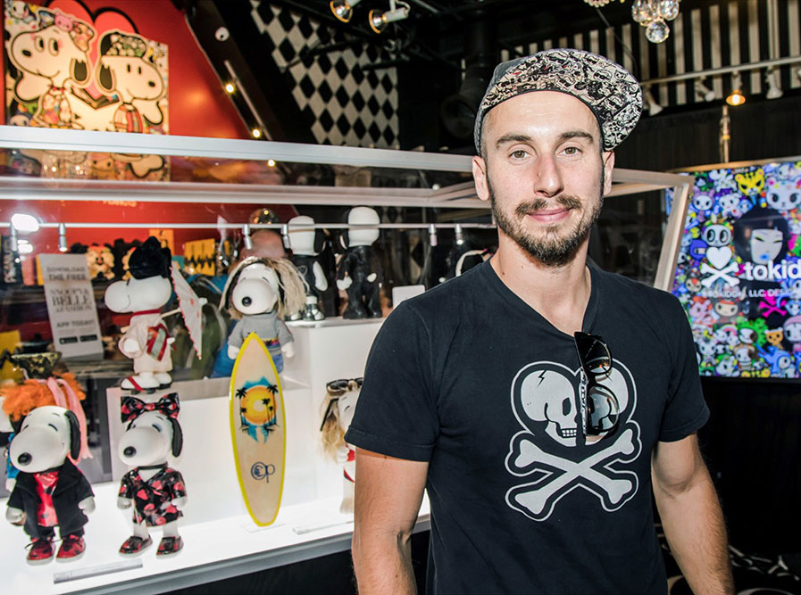 A bearded man wearing a t-shirt is standing in front of a glass display of black and white dog figurines.