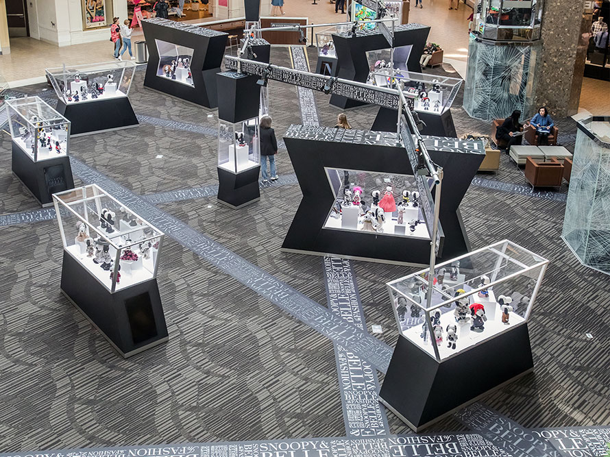 A view from above of an indoor space with several black and glass displays featuring black and white dog statues.