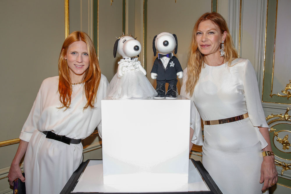 Two women, wearing white semi formal dresses, posing for a phot next to two black and white dog statues on display.