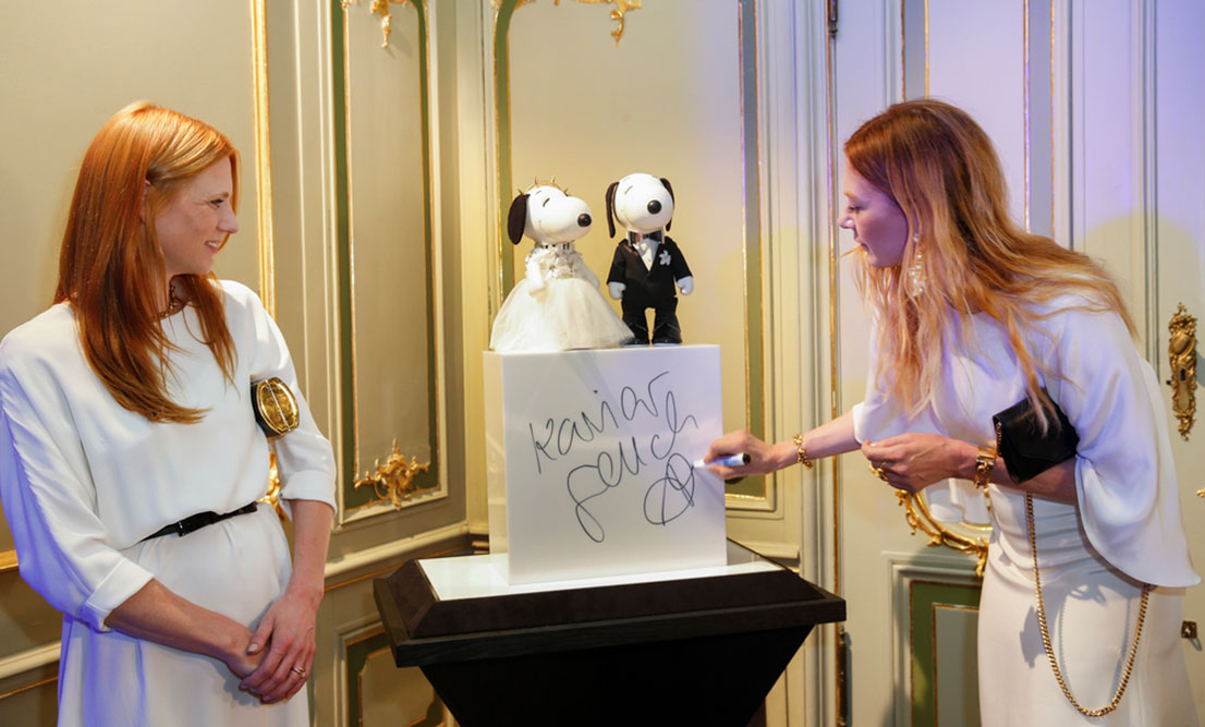 Two women, wearing white dresses, standing beside a display of two black and white dog statues. One woman is leaning over and signing her name.