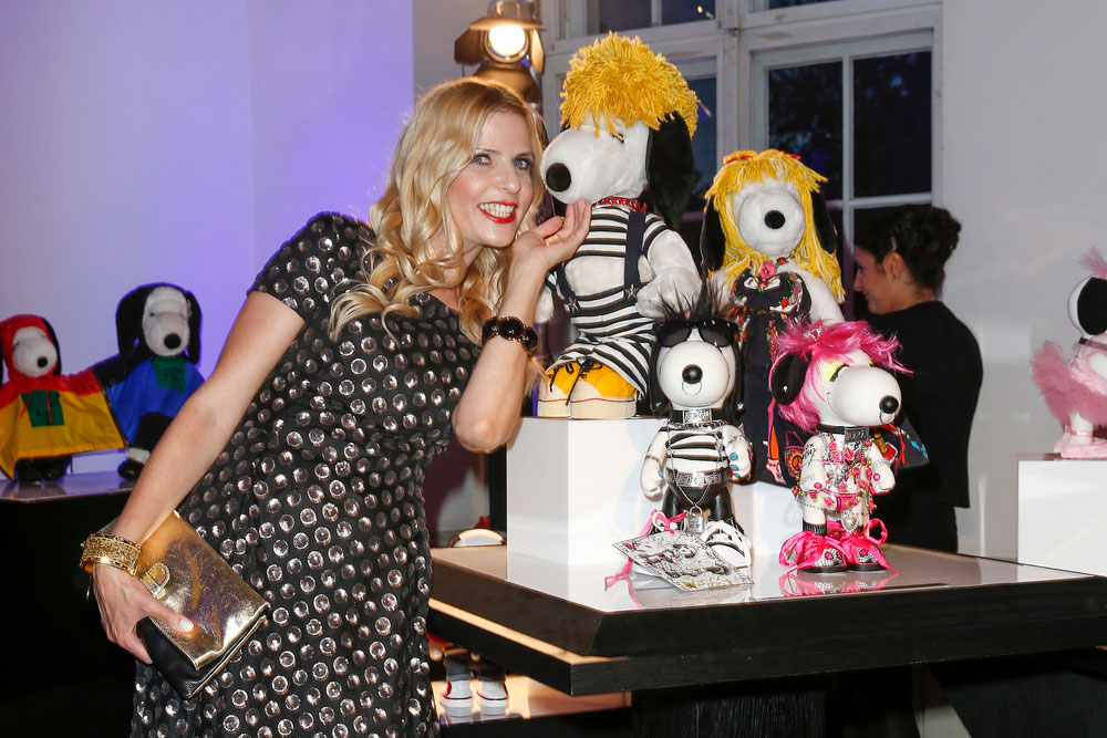 A blonde woman, wearing a black dress, leaning over towards a display of black and white dog statues at a semi formal event.