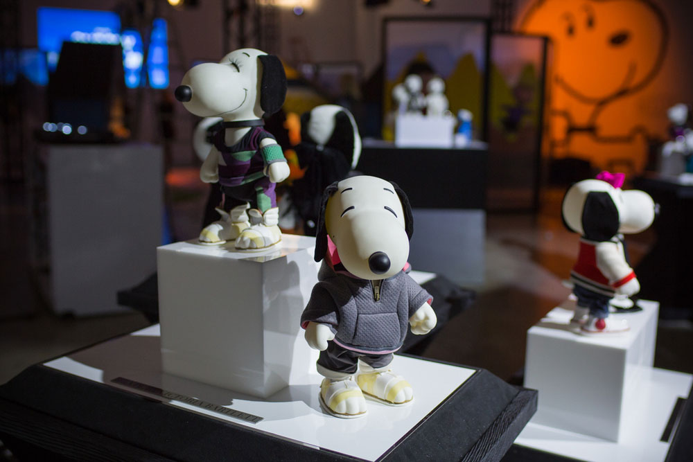 Black and white dog statues, wearing various costumes, on display in an indoor space.