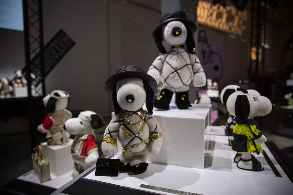 A close-up of black and white dog statues, wearing various costumes, on display in an indoor space.