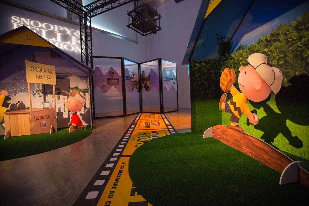 An indoor space, with dim lights. There is a large poster on the right side of a boy playing baseball and another art installation on the left side.
