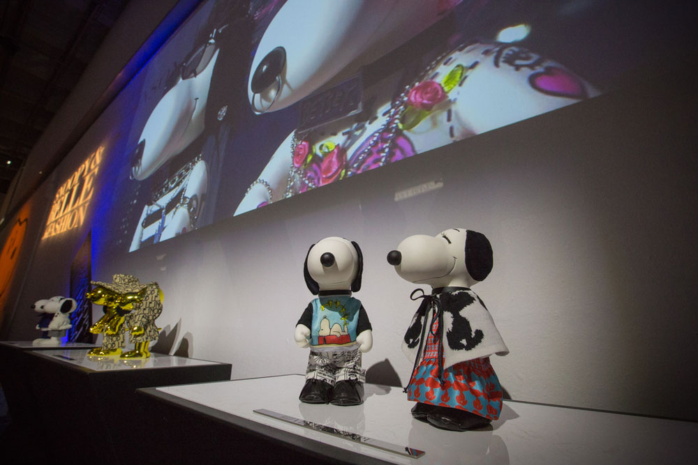 A low angle view of black and white dog statues on display, with a large television display above them.