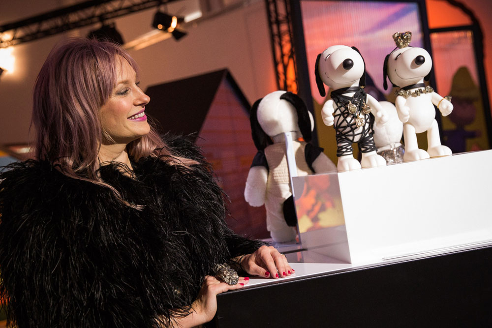 A blonde woman, wearing a black coat, is smiling and standing next to a display of small black and white dog statues at a semi formal event.