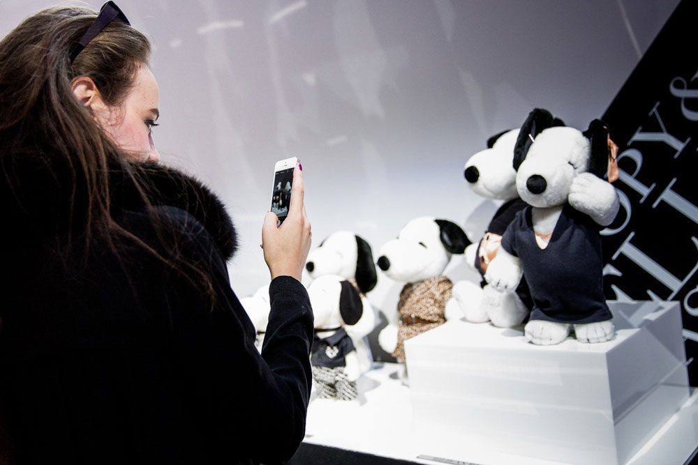 A brunette woman, wearing a black coat, taking a photo of black and white dog statues on display at a semi formal event.