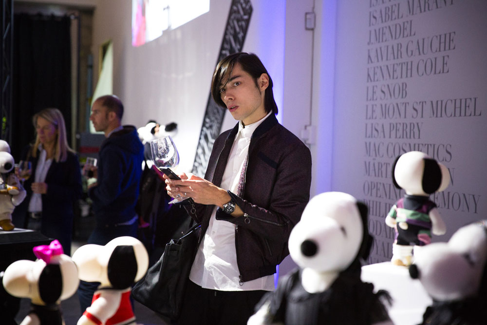 A man standing in front of black and white dog statues at a semi formal event.