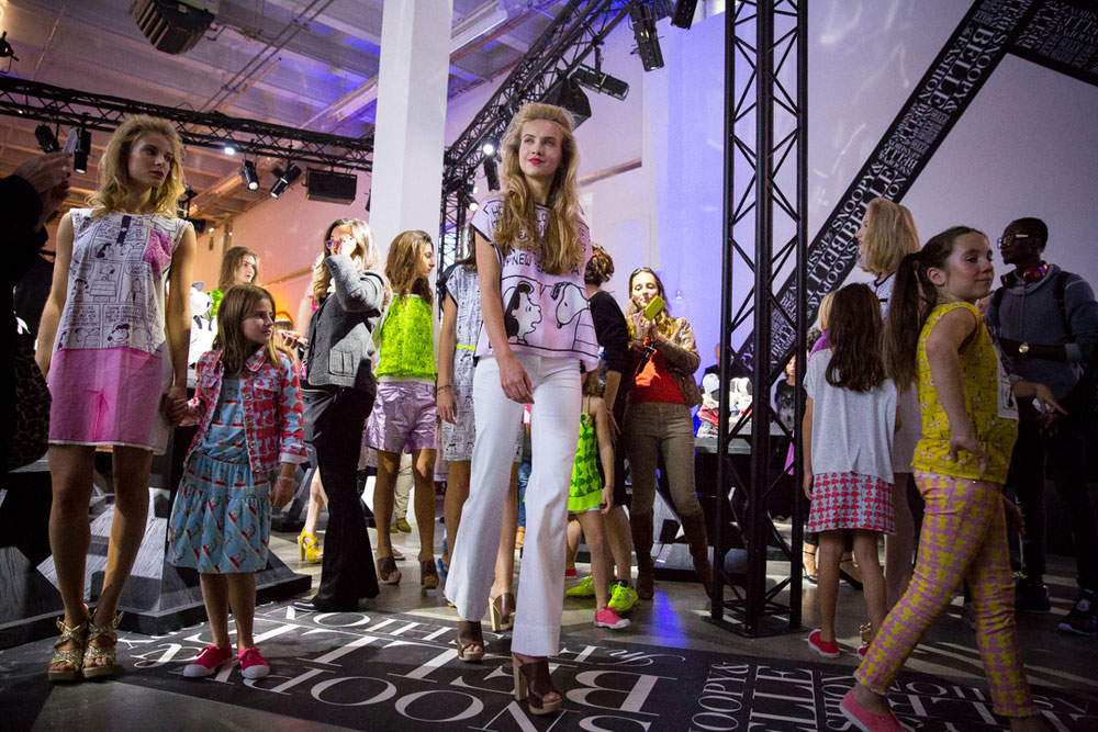 A runway show with adult and child models.