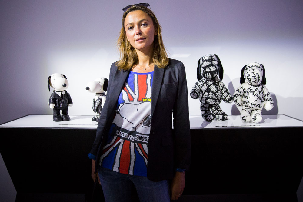 A woman with short light brown hair, wearing a black blazer and a colourful shirt, is posing for a photo in front of a display of black and white dog statues.