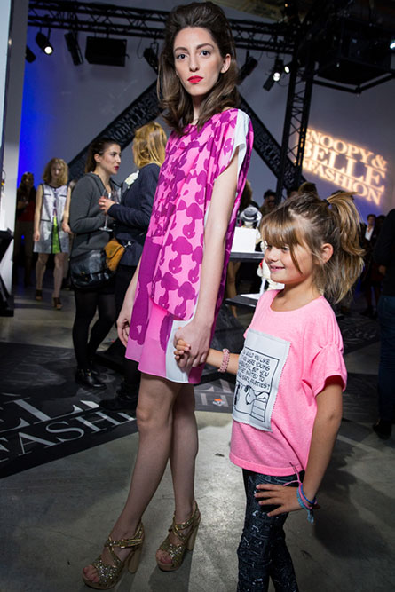 A tall, brunette woman and a young girl modeling clothes at an indoor event.