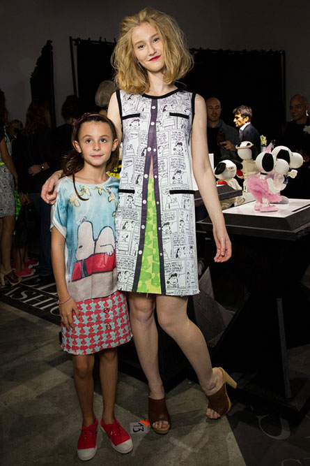 A tall, lean woman and a young girl modelling colourful clothes at an indoor event.