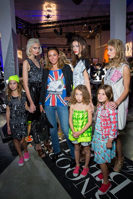 Four women and 3 young kids modelling colourful clothes at an indoor event.