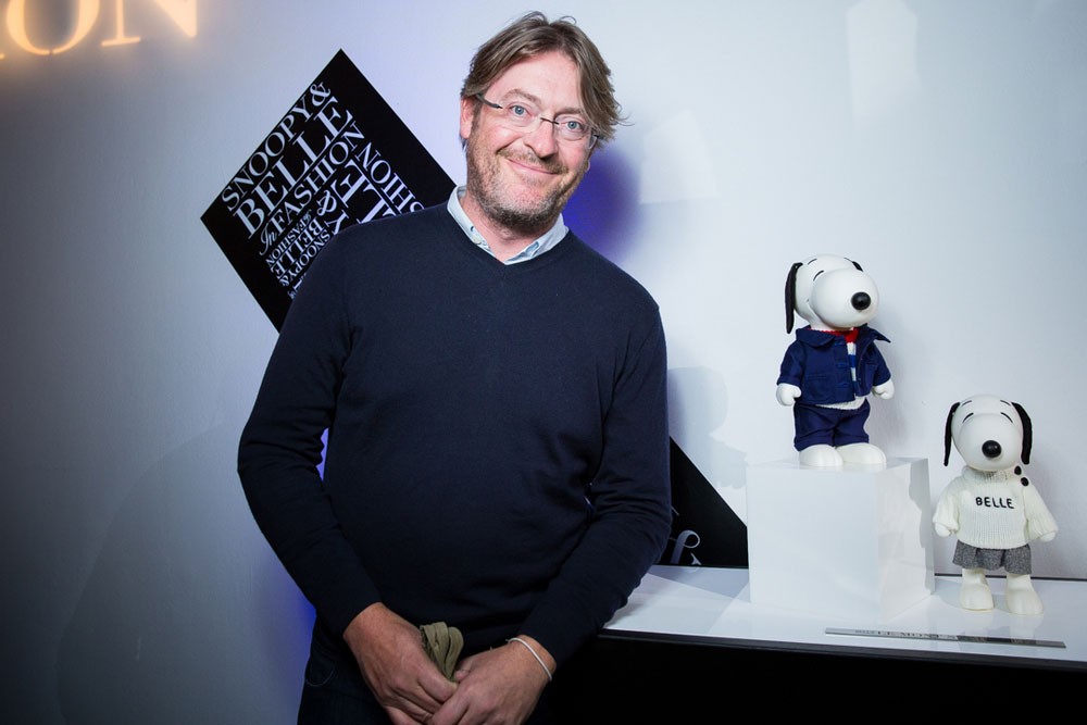A man with glasss, wearing a navy blue sweater is smiling for the camera in front two small, black and white dog statues.